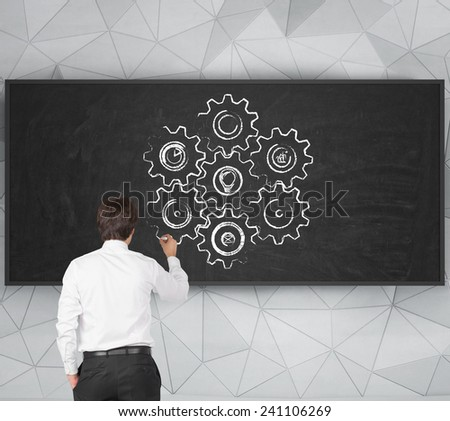 young businessman drawing cog and geers symbol on blackboard - stock photo