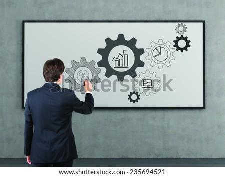 young businessman drawing cogs and gears on a whiteboard - stock photo