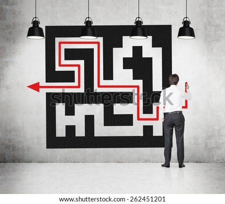 young businessman drawing labyrinth with red arrow on wall - stock photo