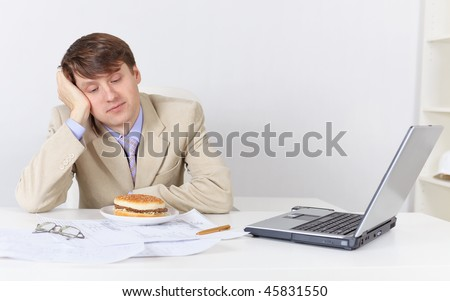 Young businessman, dreamily looking at the sandwich - stock photo