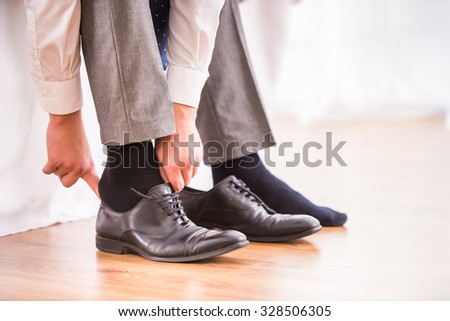 Young businessman dress shoes in the bedroom at home - stock photo