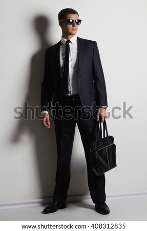 young businessman dressed in a formal suit with a handbag. Handsome man in trendy glasses