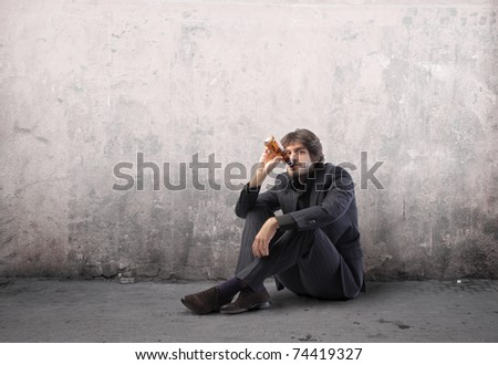 Young businessman drinking a beer on a street - stock photo