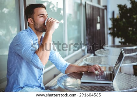 Young businessman drinking coffee beside a laptop outside a cafe - stock photo