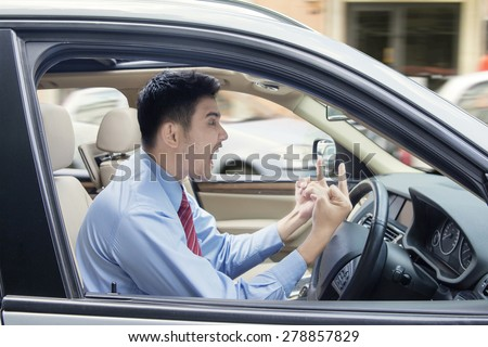 Young businessman driving a car and looks angry, showing two middle fingers and screaming