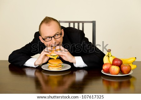 Young businessman during his lunch time eating a hamburger - stock photo