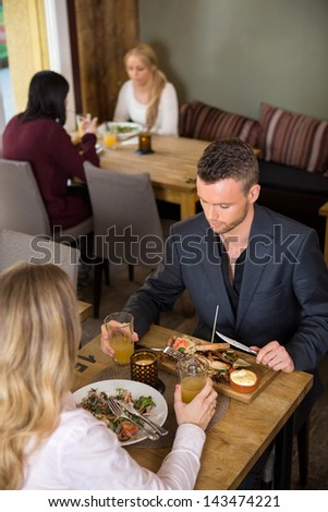 Young businessman eating food with female at cafe - stock photo