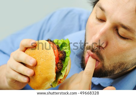 Young businessman eating hamburger, licking fingers