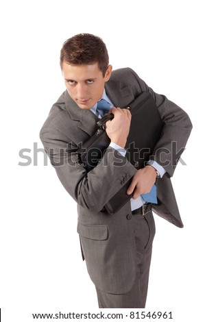 young businessman embraces a portfolio with fear. Isolated on white
