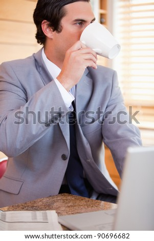 Young businessman enjoying a cup of coffee in the kitchen - stock photo