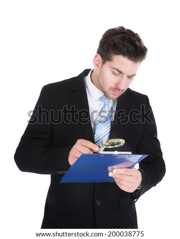 Young businessman examining document on clipboard with magnifying glass over white background - stock photo