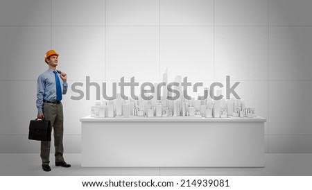 Young businessman examining model of construction project - stock photo