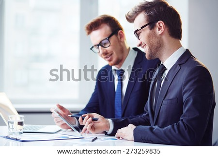 Young businessman explaining data to colleague at meeting  - stock photo