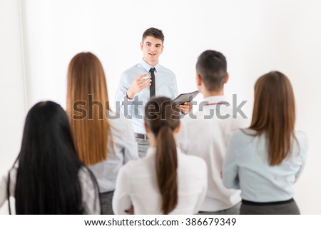 Young businessman explaining to her colleagues plan of work. The team is listening. - stock photo