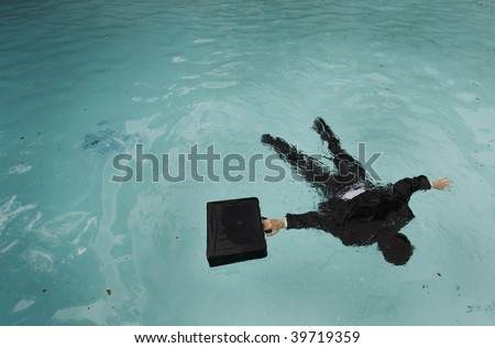 Young businessman face down in the water. - stock photo
