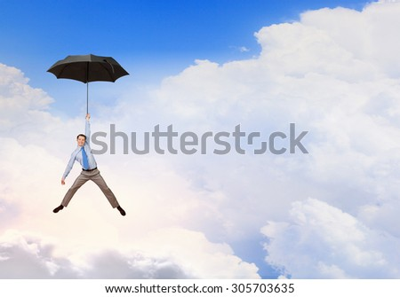 Young businessman flying high in sky on umbrella