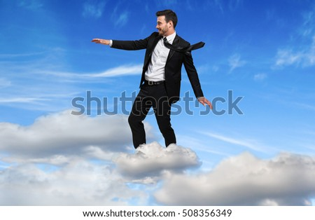 Young businessman flying over a cloud