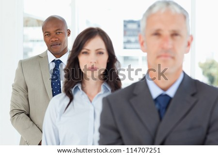 Young businessman following two serious members of his team