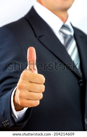 Young businessman, gesturing with his finger, well done/ good work.
