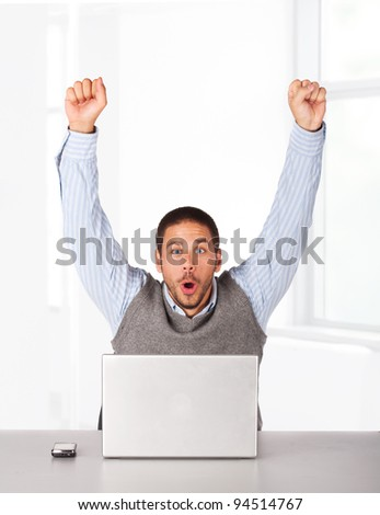 Young businessman getting good news.Gesture with arms raised and smile