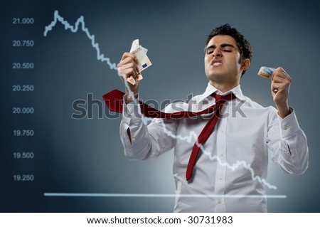 Young businessman getting mad behind a declining share. Recession and crisis concept! - stock photo