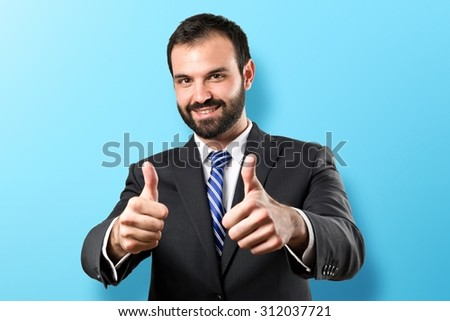 Young businessman getting OK over colorful backgound - stock photo