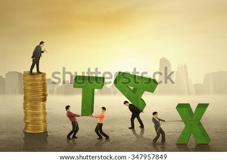 Young businessman giving order on his employees to arrange a tax text,  - stock photo