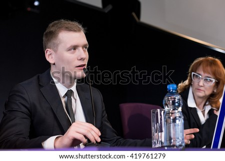 Young businessman giving presentation in conference room