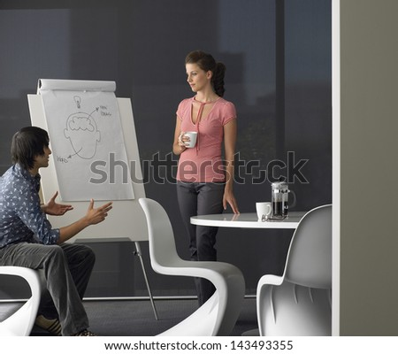 Young businessman giving presentation on flipchart to female colleague in meeting room - stock photo