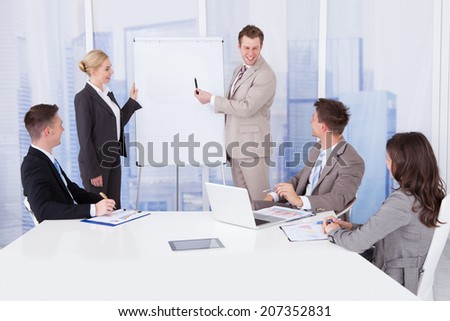 Young businessman giving presentation to colleagues in conference room