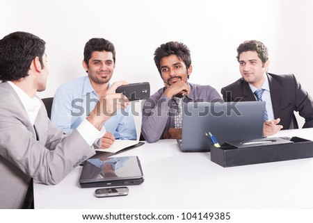 young businessman giving presentation to his colleagues, group of young multiracial businessmen in official meeting - stock photo