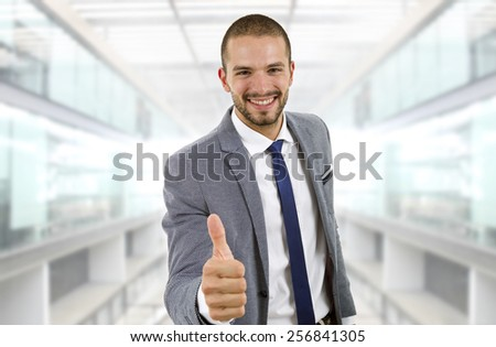 young businessman going thumb up, at the office - stock photo