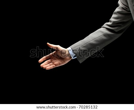 Young businessman greeting with handshake isolated on black - stock photo