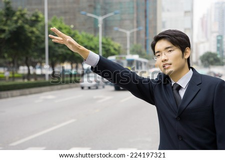 Young businessman hailing at taxi - stock photo