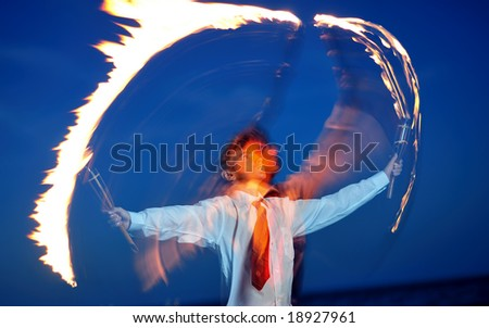 Young businessman handling flaming torch in night - stock photo