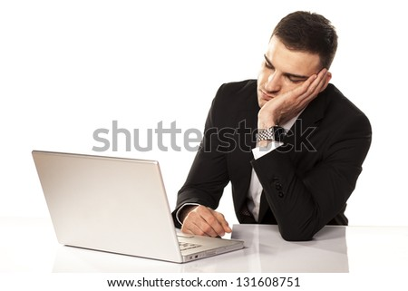 Young businessman has fallen asleep on his arm behind his laptop - stock photo