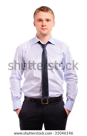 Young businessman has hidden hands in pockets of trousers, is isolated on white background.