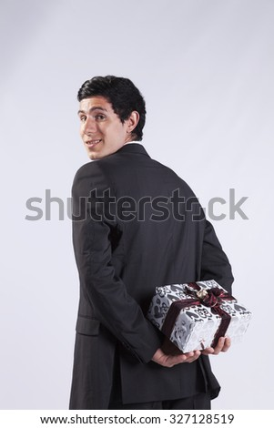 young businessman have a gift surprise to offer (isolated on gray) - stock photo