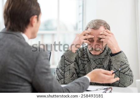 Young businessman having an interview or business meeting with sad old man. Office interior with big window - stock photo