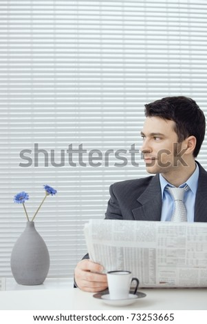 Young businessman having coffee break, sitting at office desk and reading newspaper. Copy space.? - stock photo