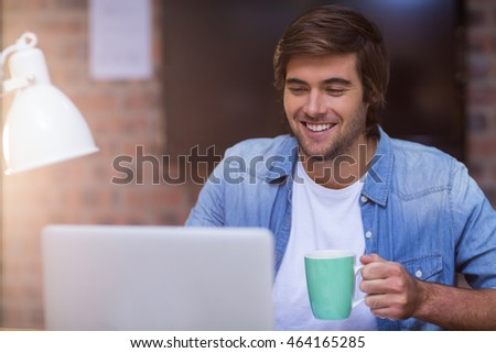 Young businessman having coffee while working on laptop in creative office