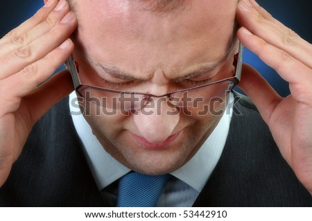 Young businessman having headache, close up image - stock photo