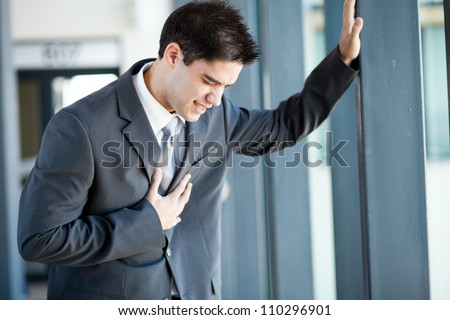 young businessman having heart attack or chest pain - stock photo