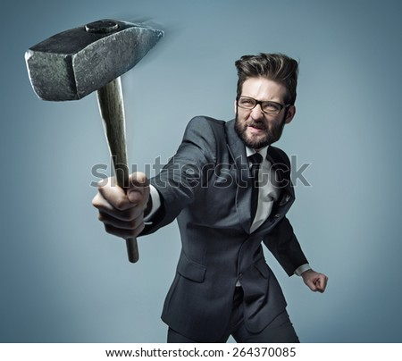 Young businessman hitting something with a hammer - stock photo