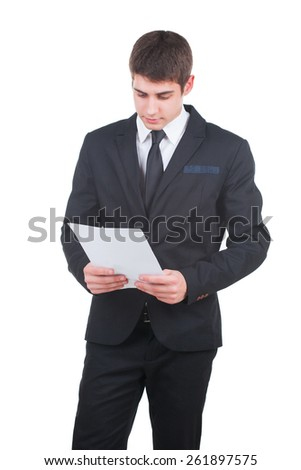 Young businessman holding a blank white paper and looking down. Studio shot - stock photo