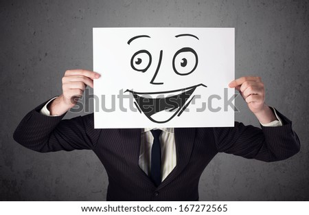 Young businessman holding a cardboard with a smile face on it in front of his head