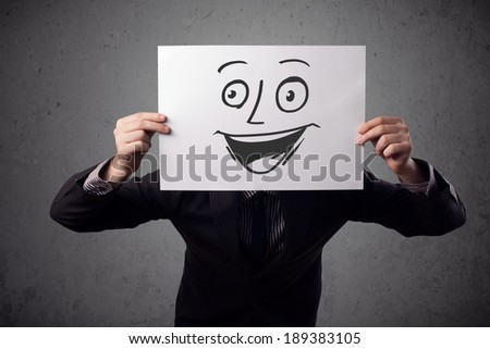 Young businessman holding a cardboard with a smiley face on it in front of his head