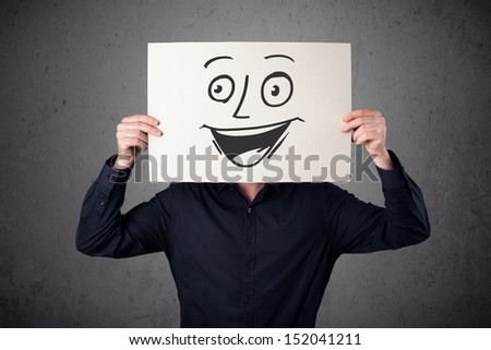 Young businessman holding a cardboard with a smiling face on it in front of his head