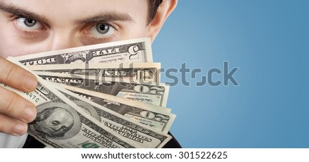 Young businessman holding a fan of dollar bills near the face on blue background with copy-space