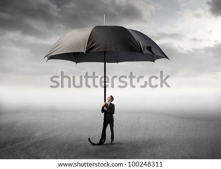 Young businessman holding a giant umbrella under stormy sky - stock photo